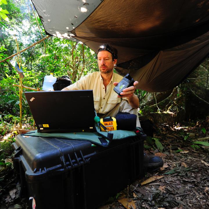 man working on laptop under tent