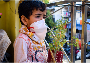 Masked child holding a plant