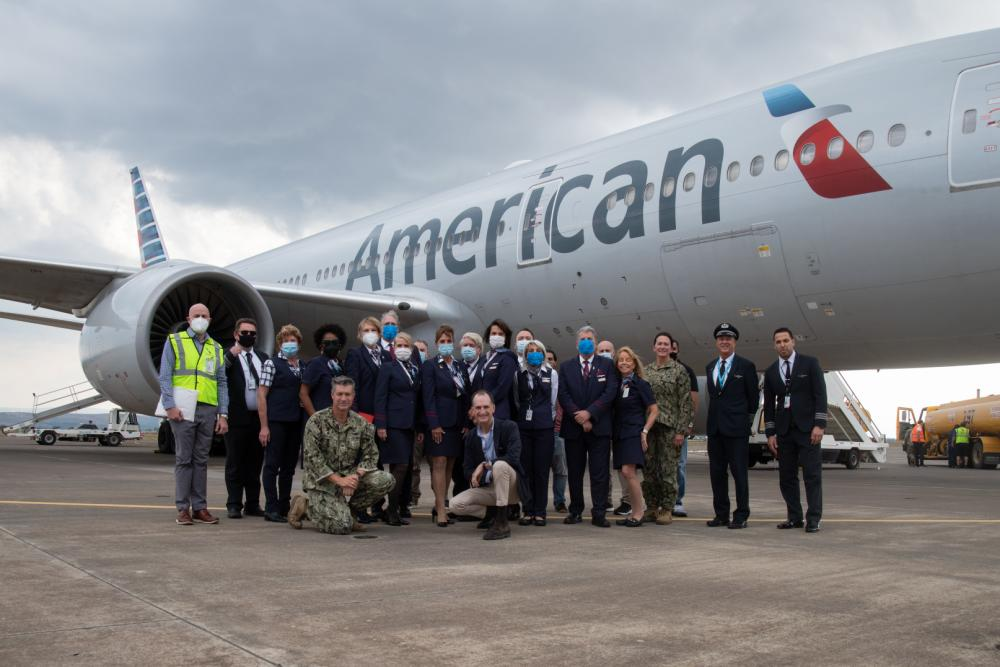 Group standing by American Airlines plane
