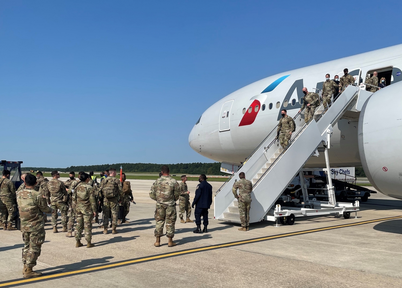 Troops disembarking from plane