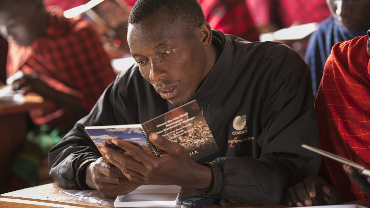 This ruby miner from Longido, Tanzania, is captivated by the lessons in recognizing quality and value in rough gem material. Selecting Gem Rough: A Guide for Artisanal Miners, authored and produced by GIA, is distributed for free to miners in East Africa. The booklet comes with a translucent white tray where miners can sort and examine rough. Photo by Robert Weldon/GIA (c) 2019