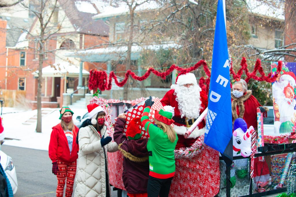 Santa Claus and volunteers from United Airlines deliver gifts at Warren Village for residents.