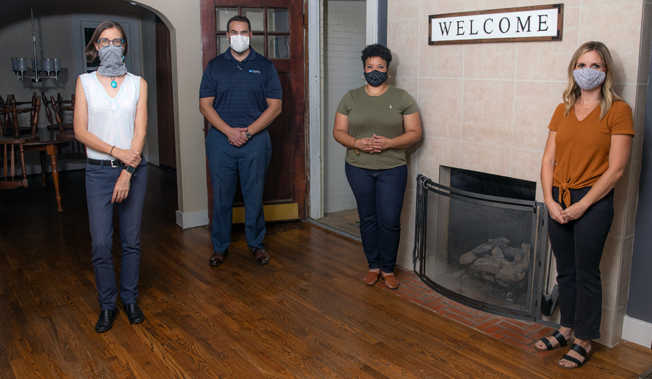 Image of four volunteers wearing masks inside the house