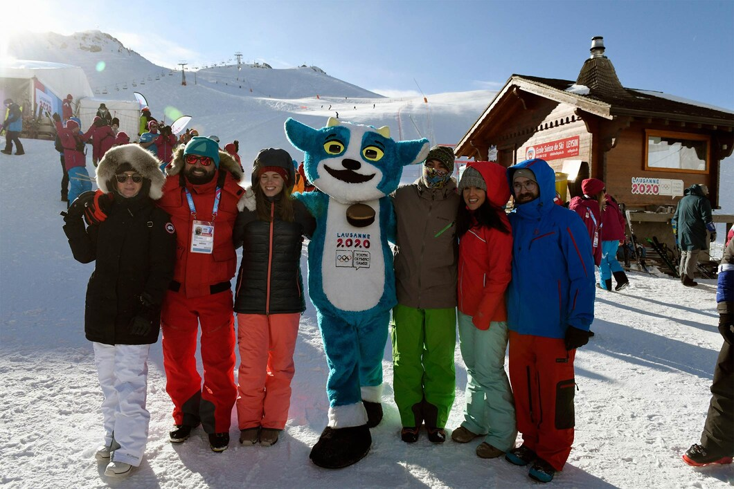 six people pose with youth olympic games mascot