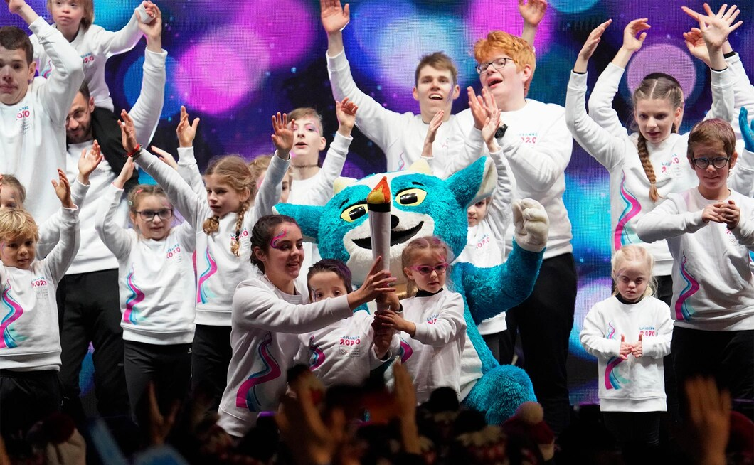 A group of kids celebrates with youth olympic games mascot