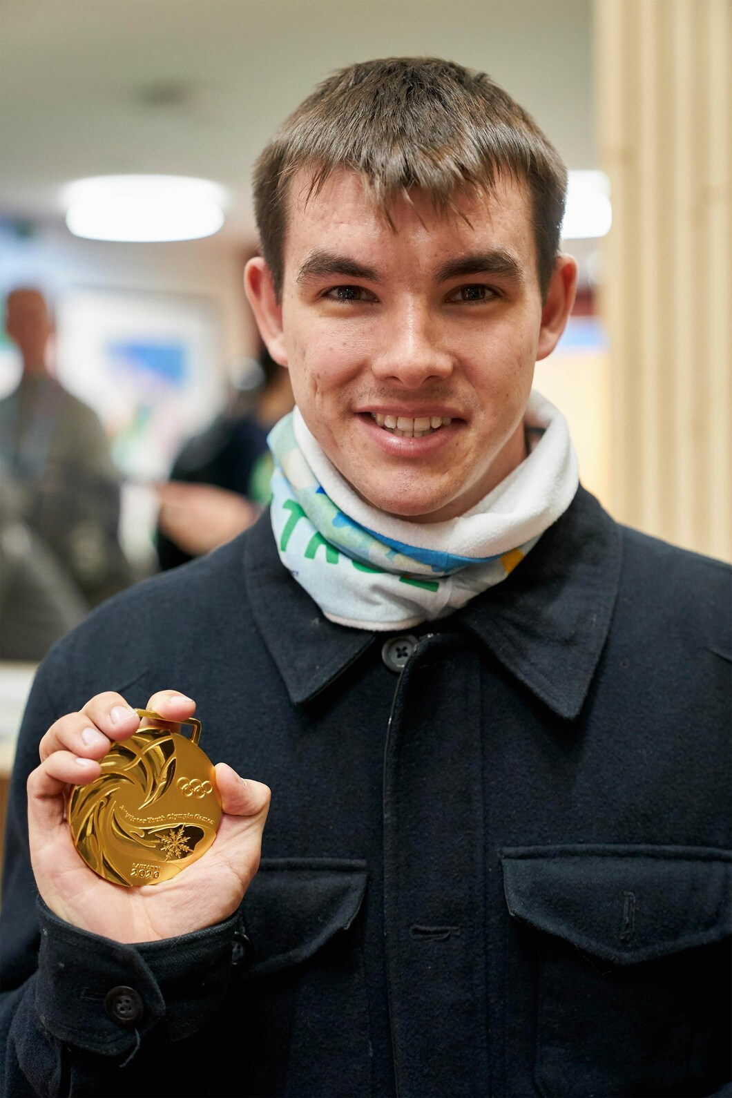 young man holding youth olympic games gold medal