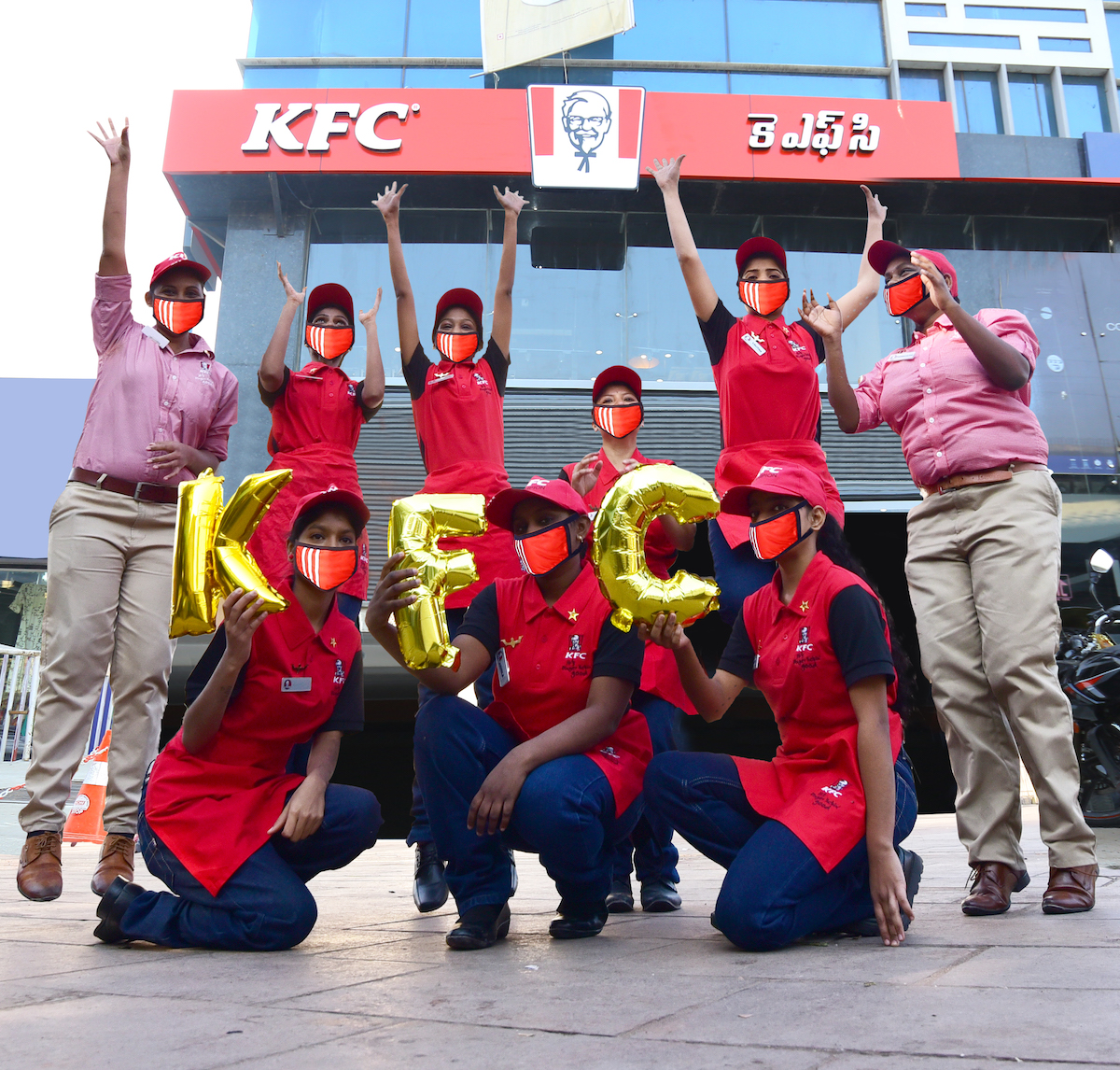 """Workers celebrate in front of newly opened KFC, holding balloons that read """"KFC"""""""