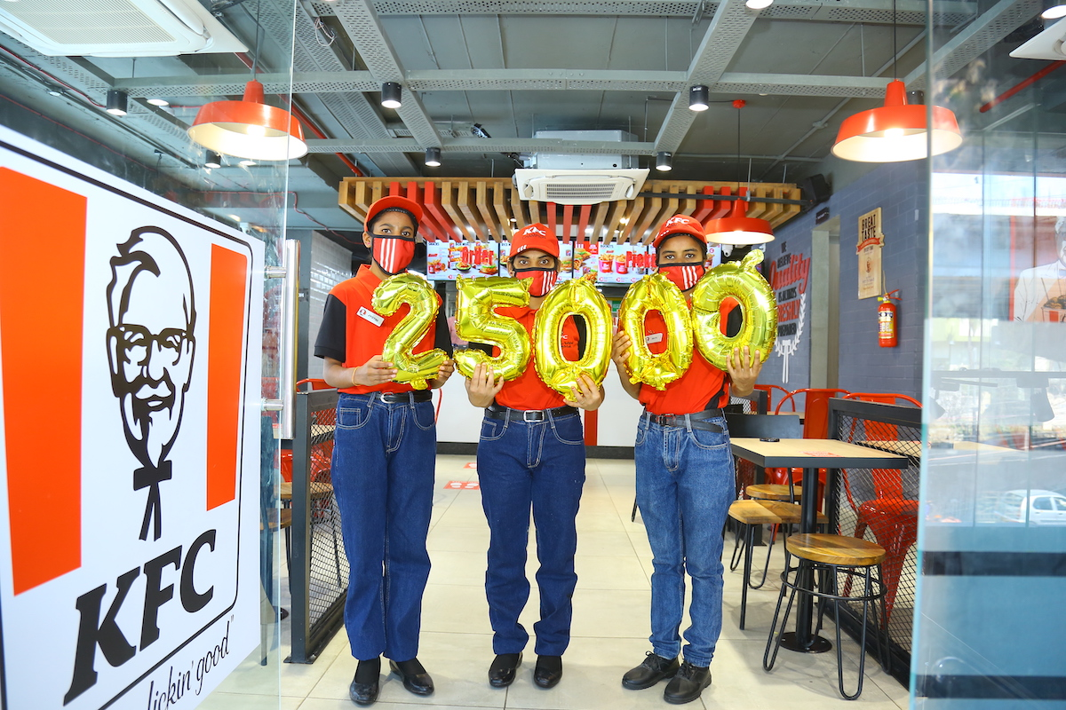 """Workers standing inside new KFC location hold balloons reading """"25,000"""""""