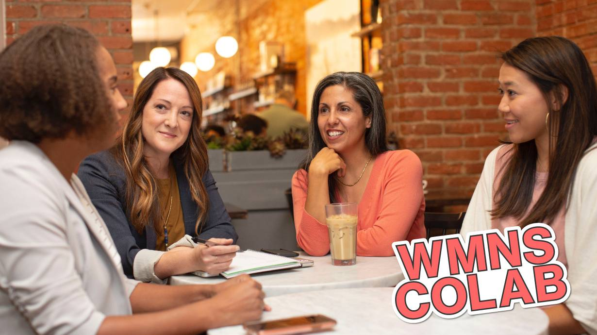 4 woman sitting around a table talking. Image reads: WMNS COLAB