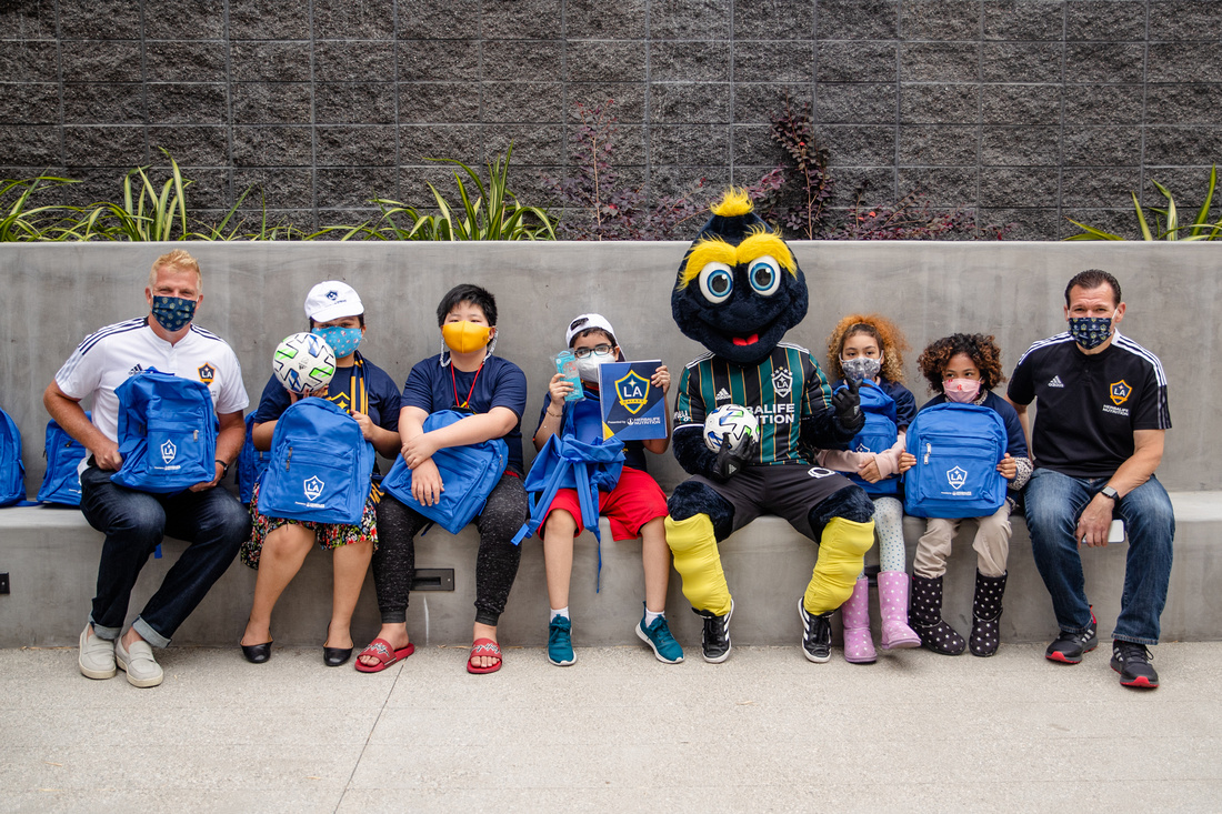 """LA Galaxy First Team Goalkeeping Coach and LA Galaxy Legend Kevin Hartman (left), LA Galaxy Broadcaster Joe Tutino (right) and LA Galaxy mascot Cozmo congratulate youth participants from Little Tokyo Service Center after """"breaking in"""" their new soccer equipment and LA Galaxy swag at the new Terasaki Budokan complex in downtown Los Angeles on May 10 2021"""