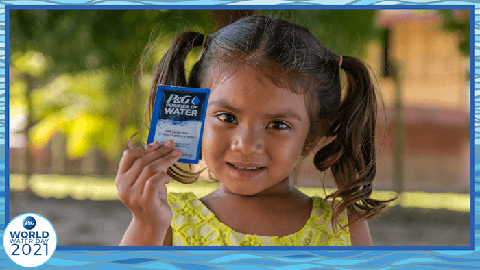 A little girl holding P&G water purification packet.