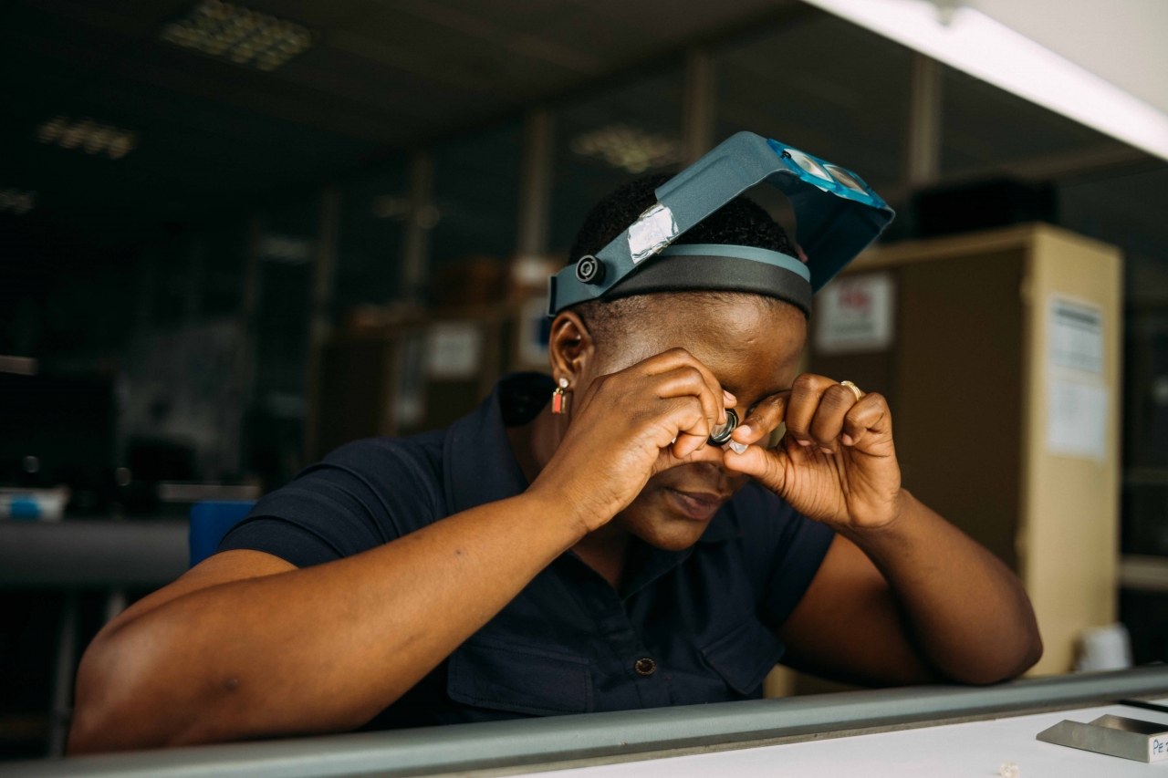 De Beers Employee Sorting through Rough Diamonds with a Loupe at the Company's Global Sightholder Sales (GSS) Headquarters in Botswana. Photo: De Beers Group.