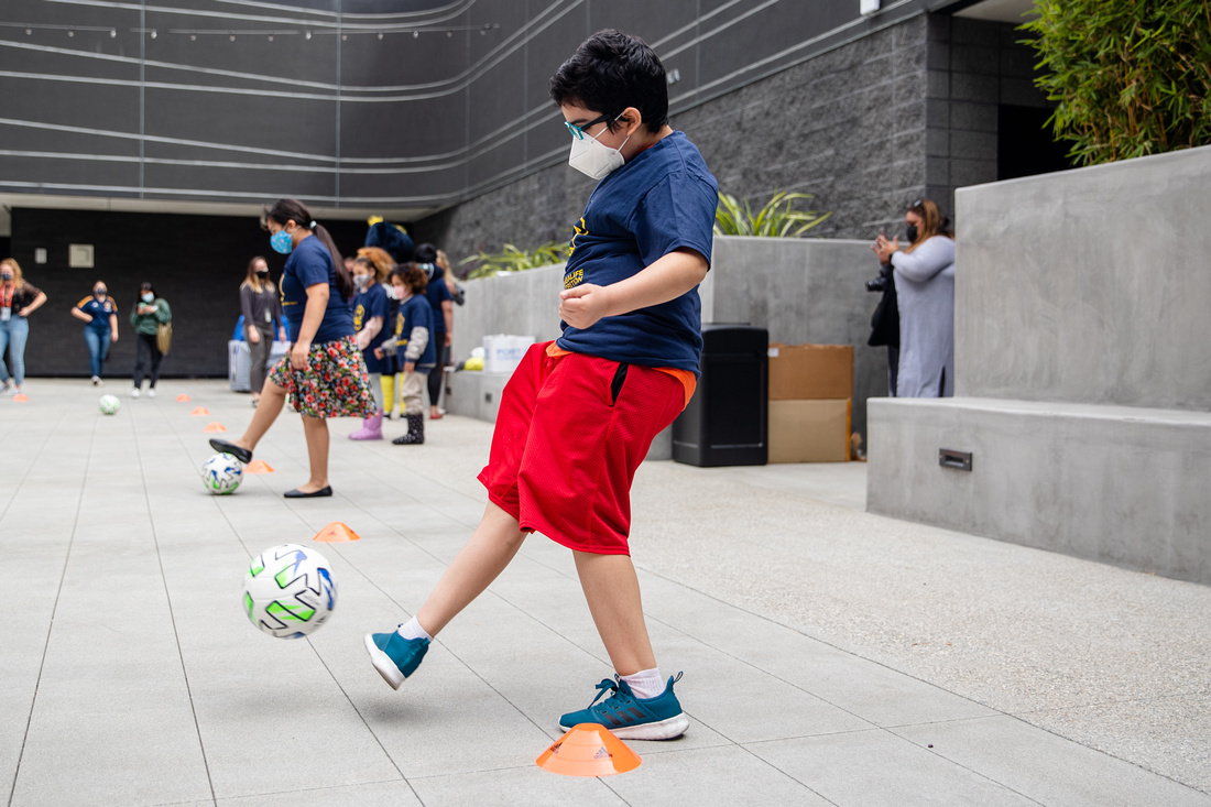 Youth participants from Little Tokyo Service Center test out the newly donated soccer equipment from the LA Galaxy with club staff at the new Terasaki Budokan complex in downtown Los Angeles on May 10 2021