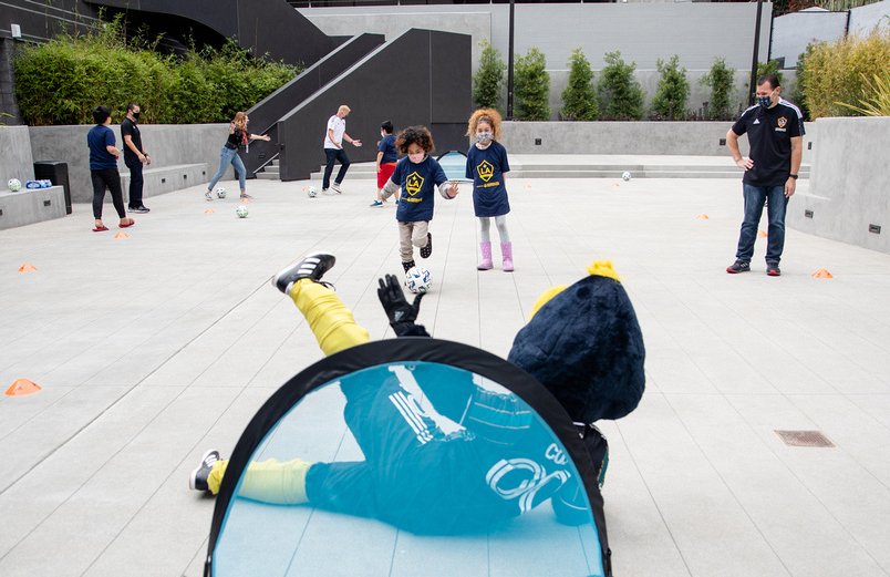 Youth participants from Little Tokyo Service Center test out the newly donated soccer equipment from the LA Galaxy with club mascot Cozmo at the new Terasaki Budokan complex in downtown Los Angeles on May 10 2021
