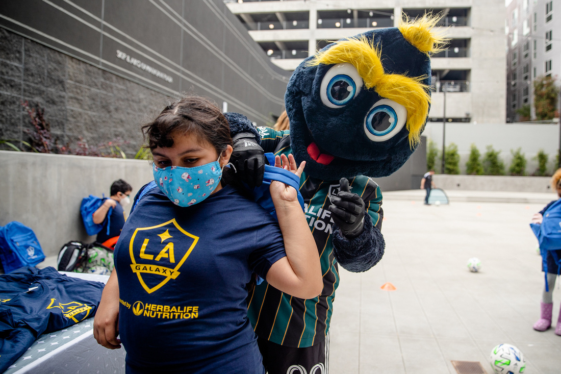 LA Galaxy mascot Cozmo passes out club swag to youth participants from Little Tokyo Service Center during a soccer equipment drop-off at the new Terasaki Budokan complex in downtown Los Angeles on May 10 2021