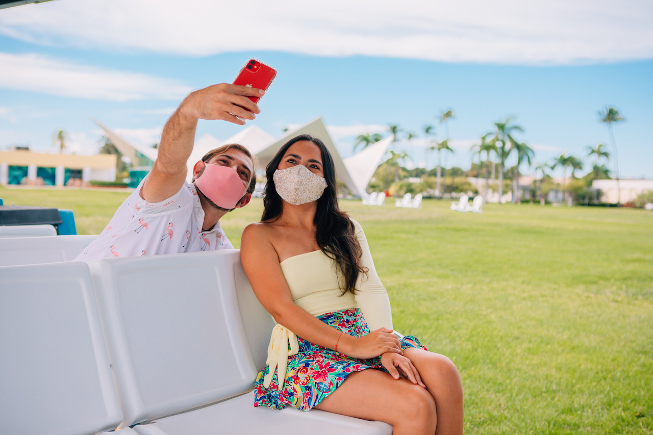 Young man and woman take a selfie while wearing masks