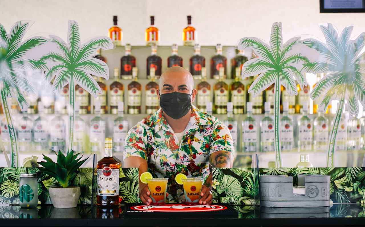 Image of a bartender serving drinks while wearing a face mask