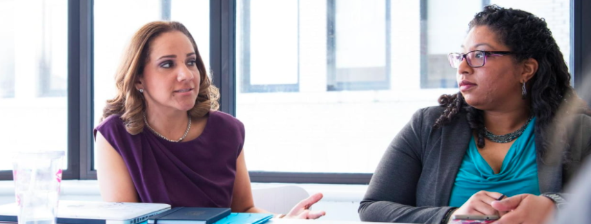 two women speak together in an office