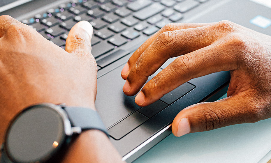 person's hands working on a laptop