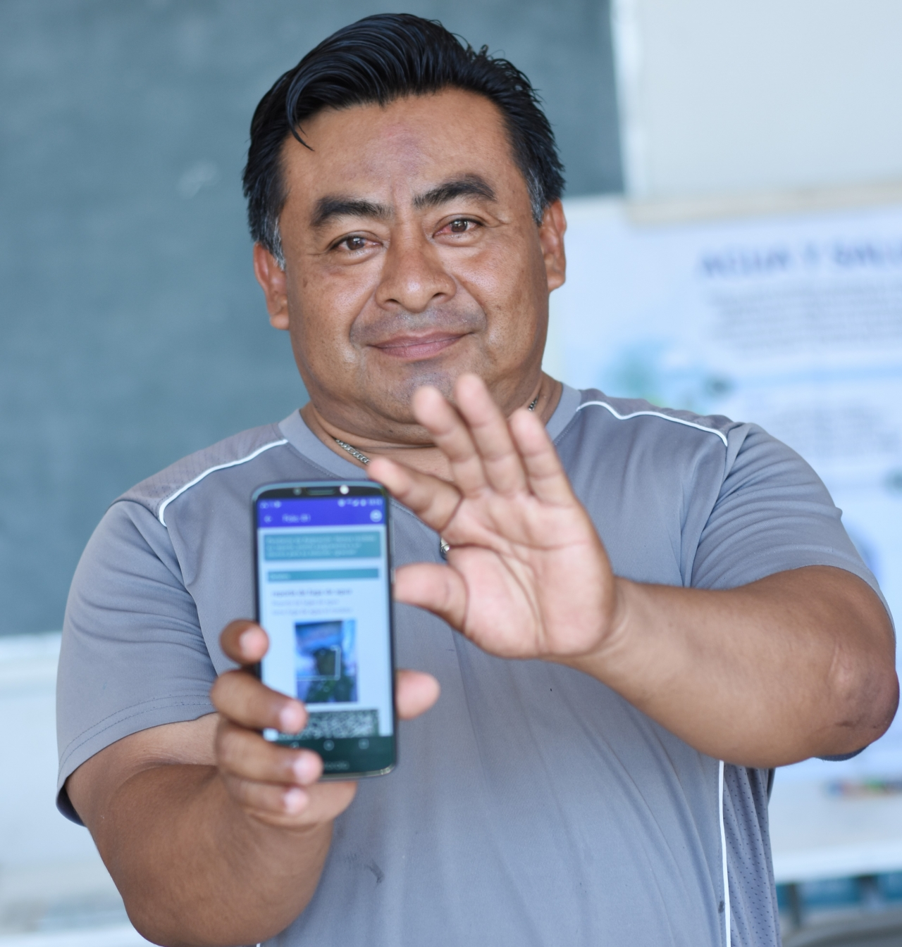 Man holding his phone, showing the app