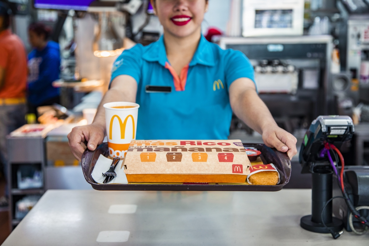 employee holding out a tray of food