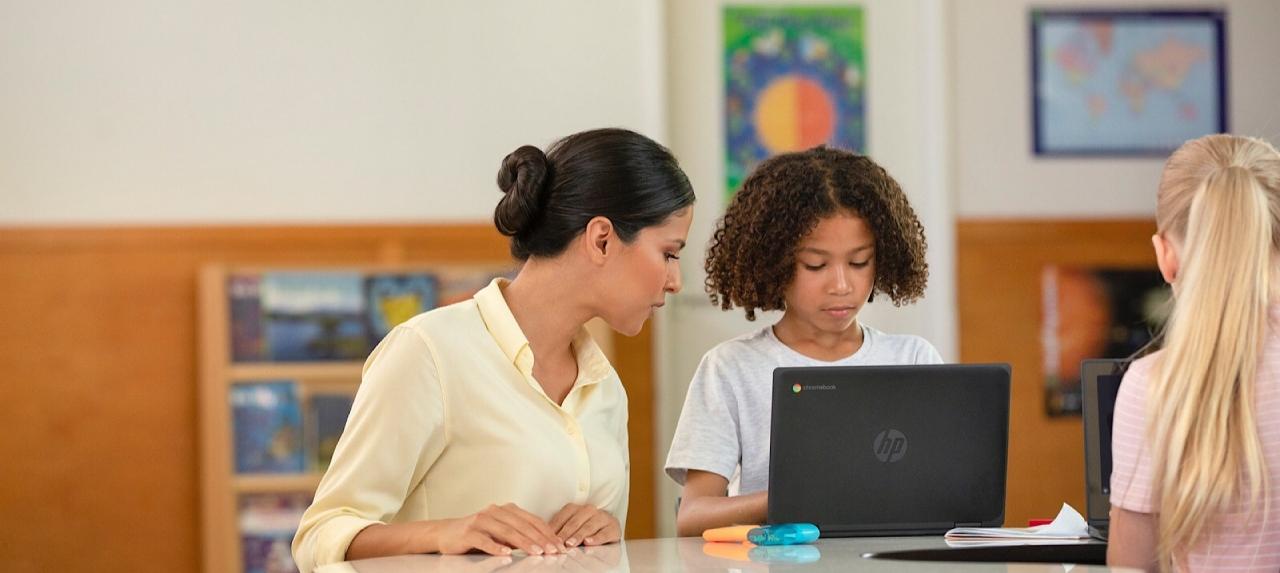 teacher helping a student on a laptop
