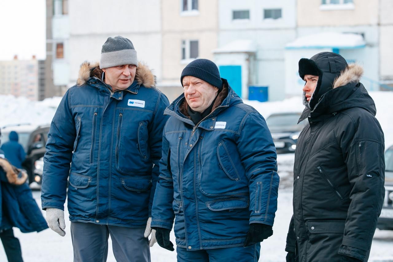Image of three men wearing parkas