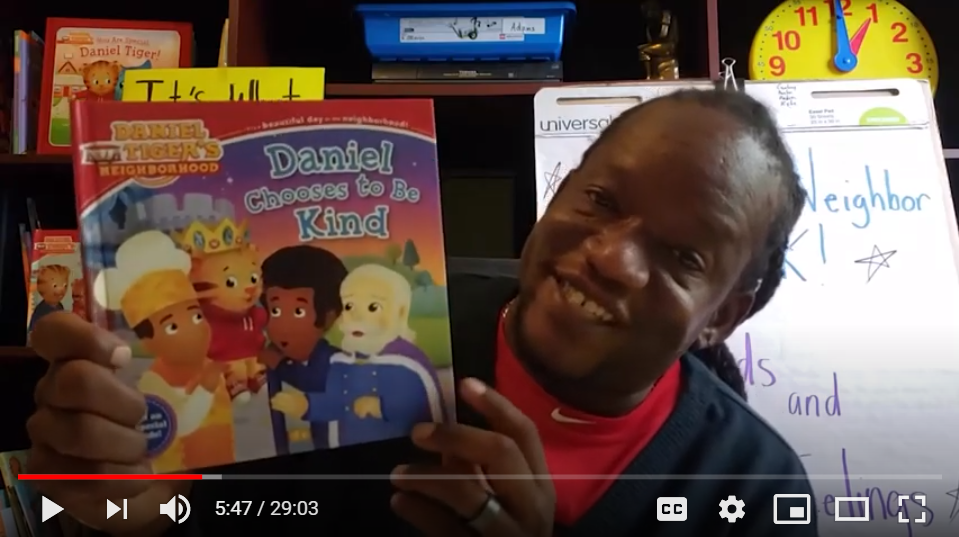 person holding up children's book while smiling