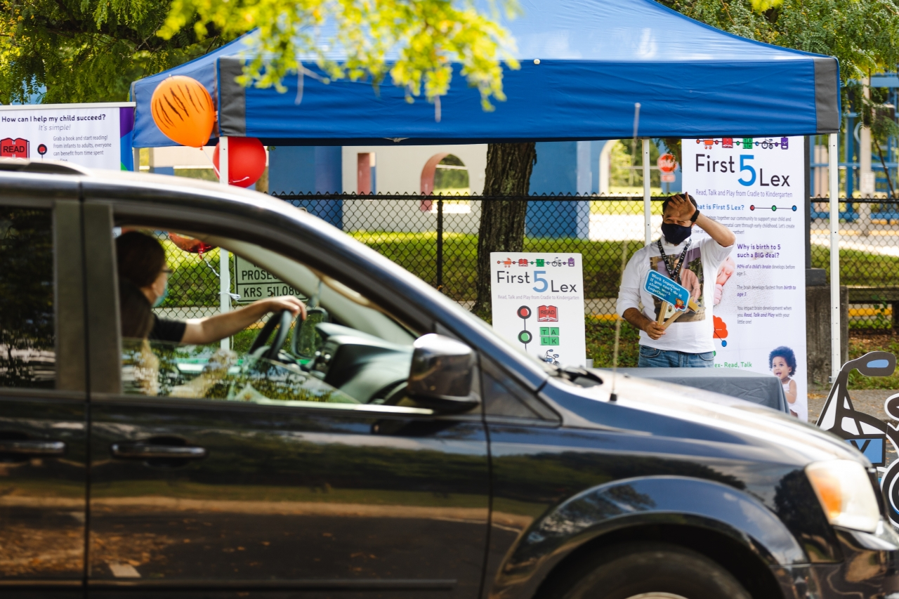 person driving a car pulls up to a community event