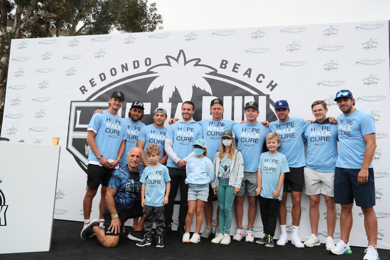 LA Kings players, event emcee Daryl Evans and children pose for a photo after greeting the crowd at the annual LA Kings 5K benefitting the LA Kings Care Foundation and Hydrocephalus Association on September 18, 2021 in Redondo Beach, Calif.