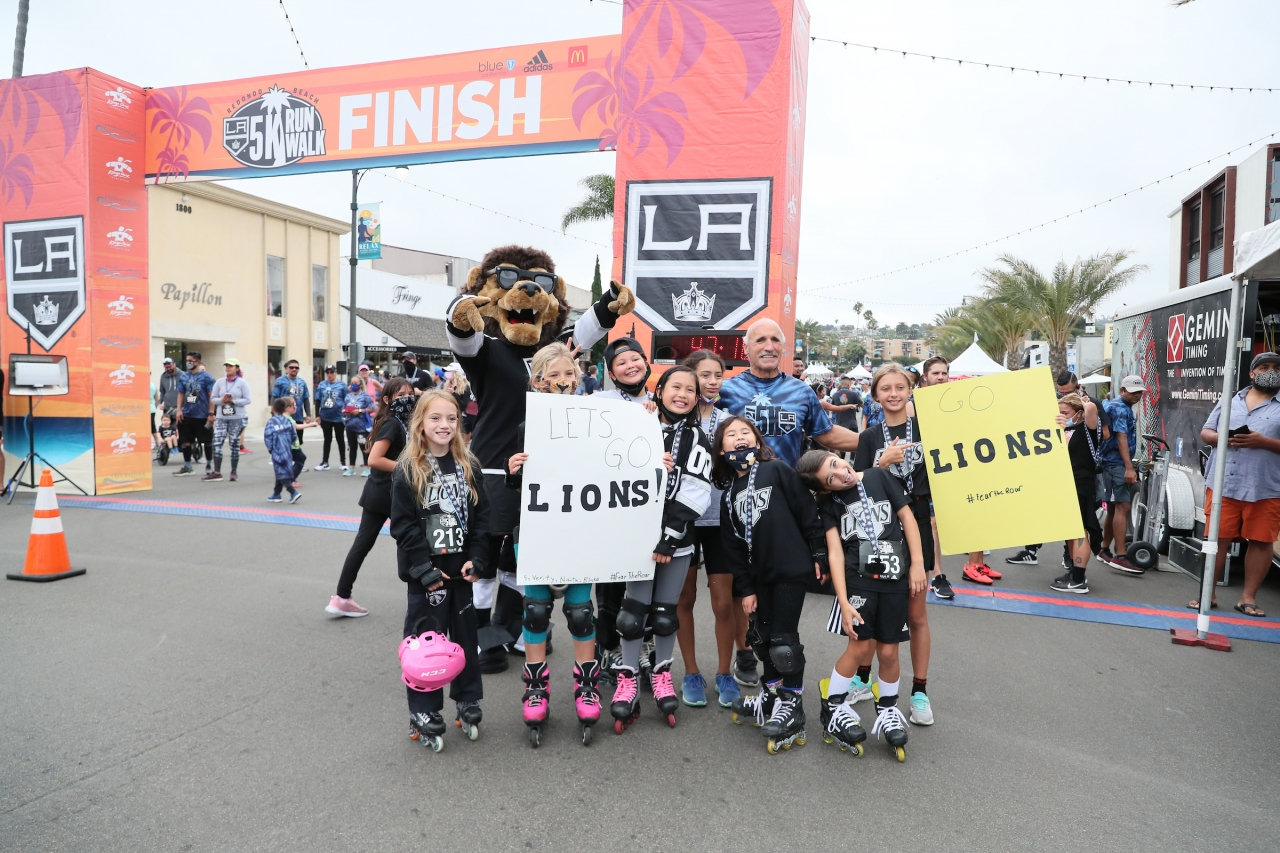 LA Kings mascot Bailey and Daryl Evans cheer on participants with members of the LA Lions, the club's youth girls club at the annual LA Kings 5K benefitting the LA Kings Care Foundation and Hydrocephalus Association on September 18, 2021 in Redondo Beach, Calif.