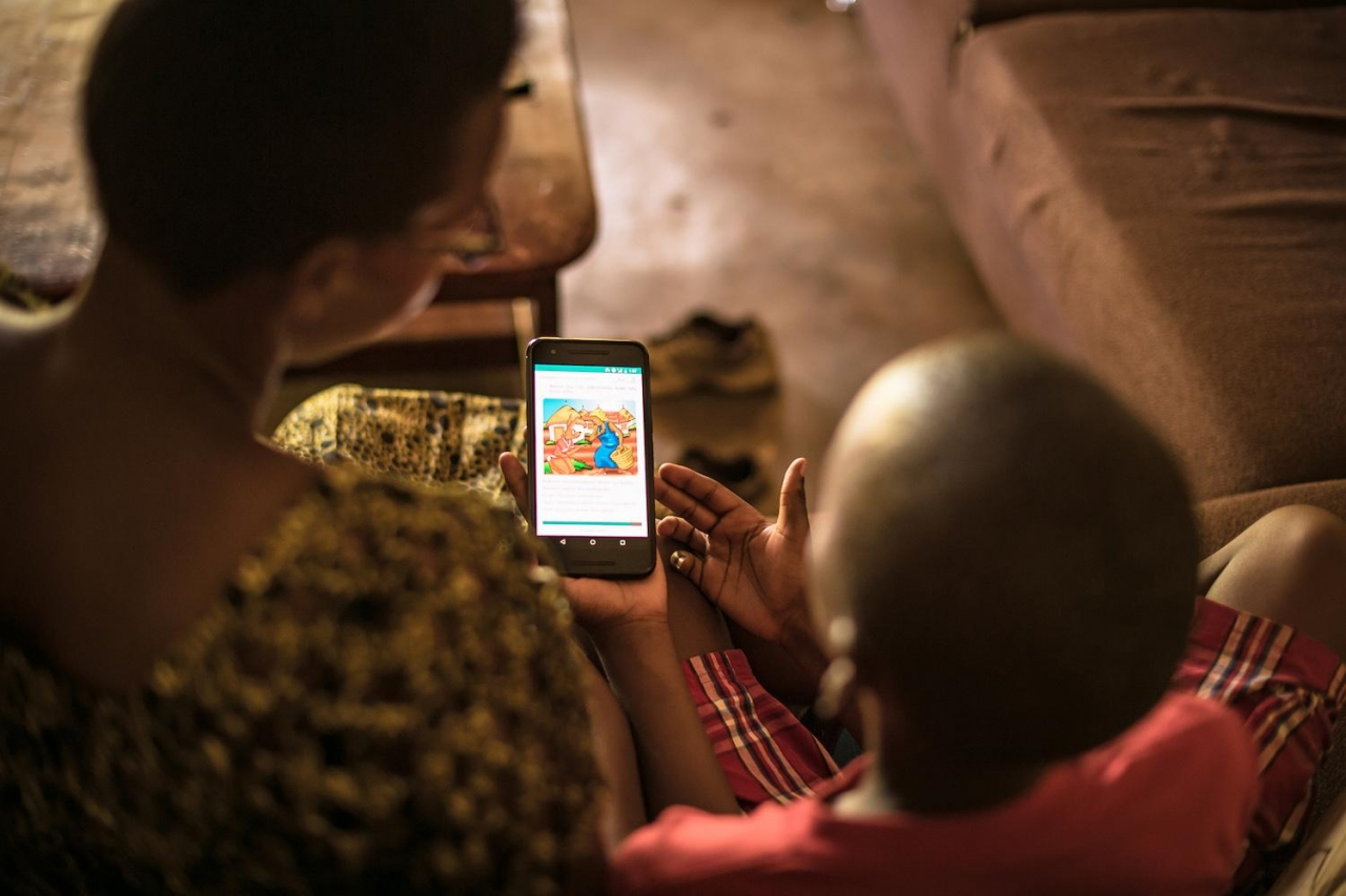 Parent and child reading on phone together