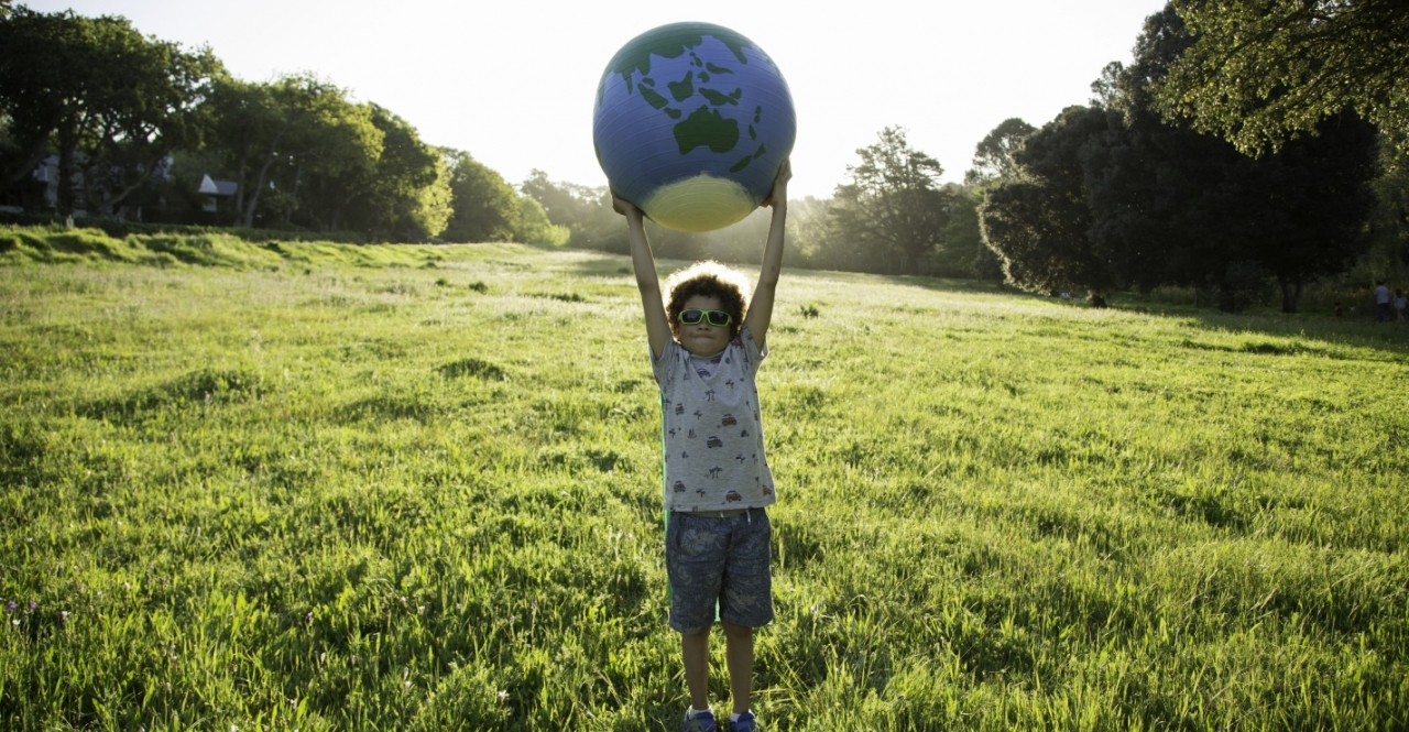 Child holding a globe above his head in a field