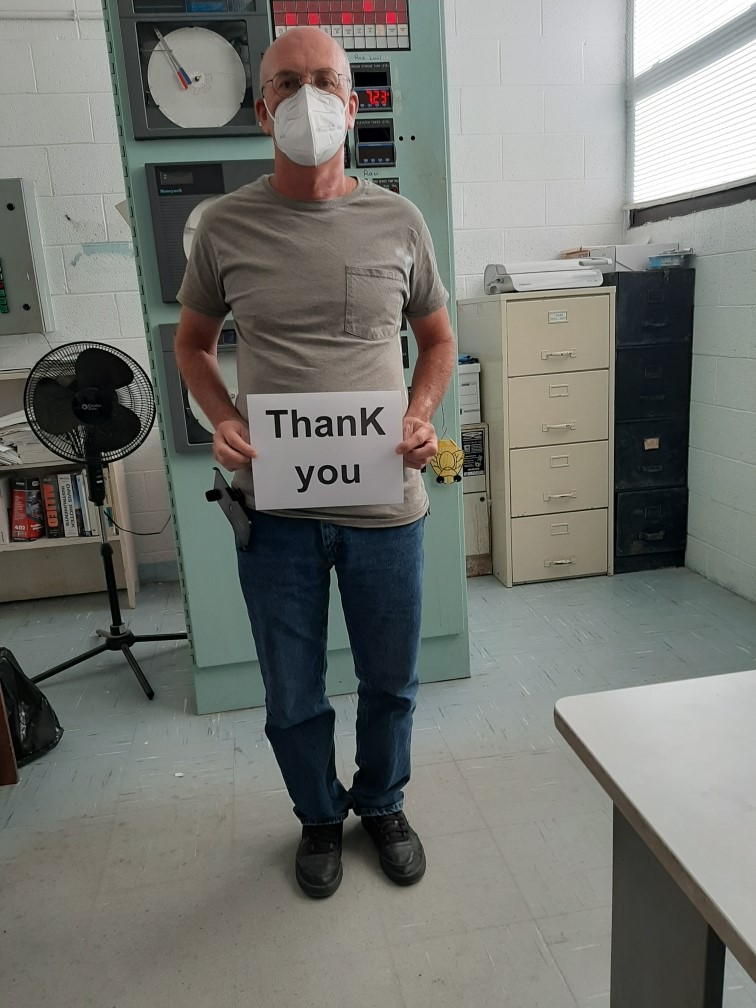 "A man wearing a mask and holding a sign reading, ""Thank You"""