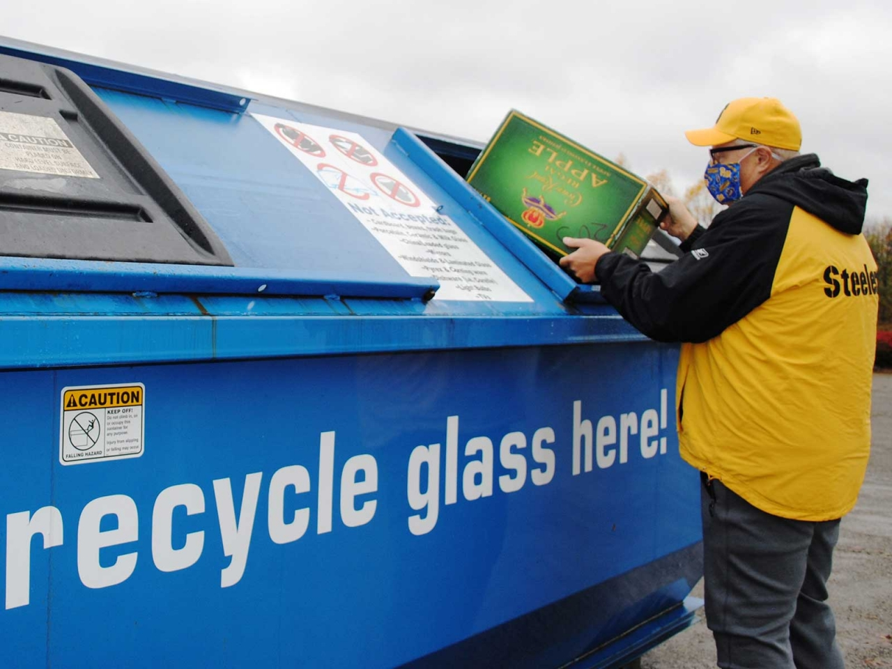person putting glass recycling into a bin