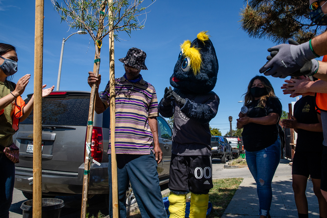 LA Galaxy mascot Cozmo and LA Galaxy and TreePeople staff congratulate a Watts resident in Los Angeles on the successful planting of a new tree in front of his home