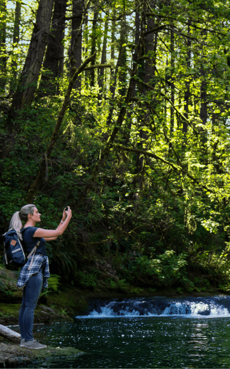 hiker taking a picture of a stream and trees