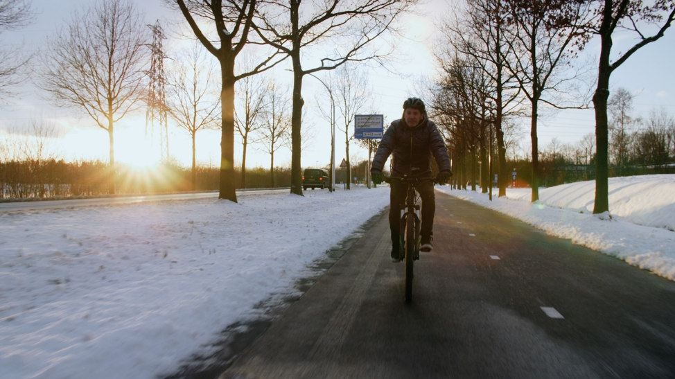 person riding a bike on a bike path in winter