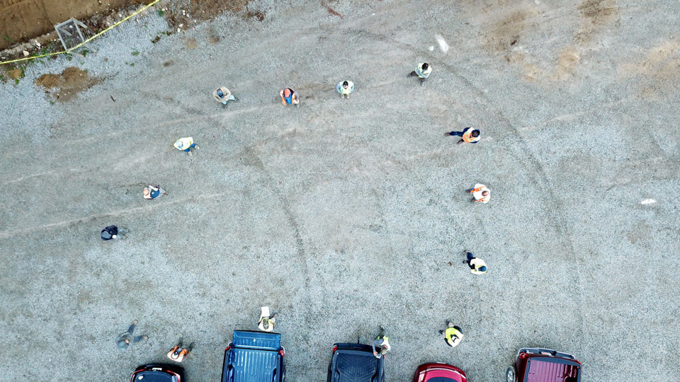 bird's eye view image of several people standing spaced apart in a parking lot