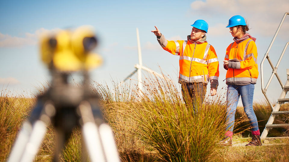 two workers with safety jackets working in a field