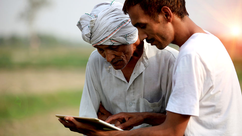 Two men looking at a tablet outside