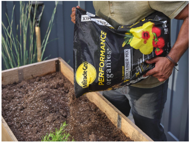gardener pouring ScottsMiracle Gro into a raised plant bed