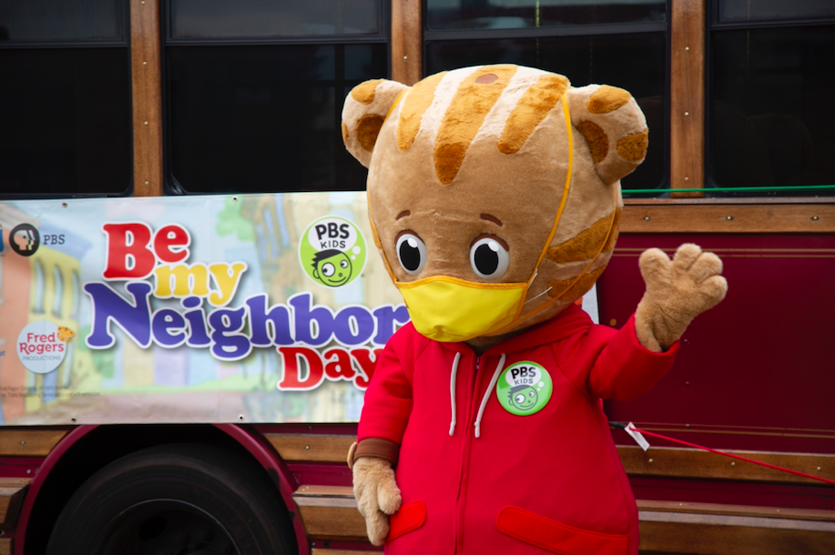 person in daniel tiger costume waves at crowd