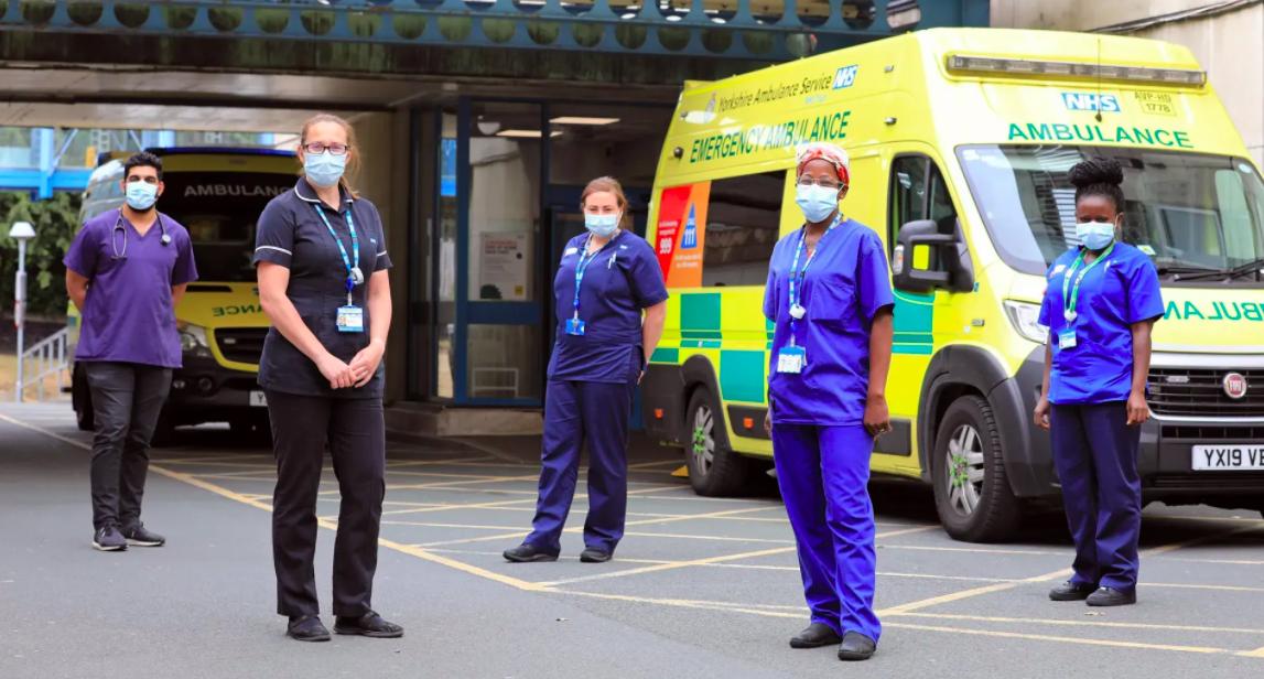 Doctors and Nurses posing near an ambulance