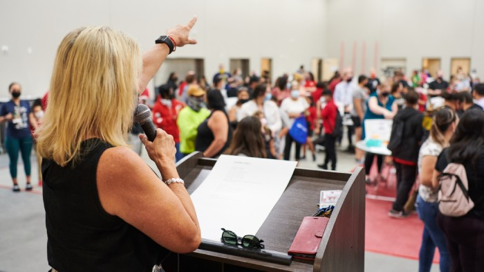 Principal Fairless directs families to stations in the school's multipurpose room. Credit: Saeed Rahbaran