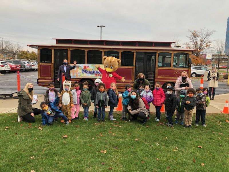 person in daniel tiger costume poses with children