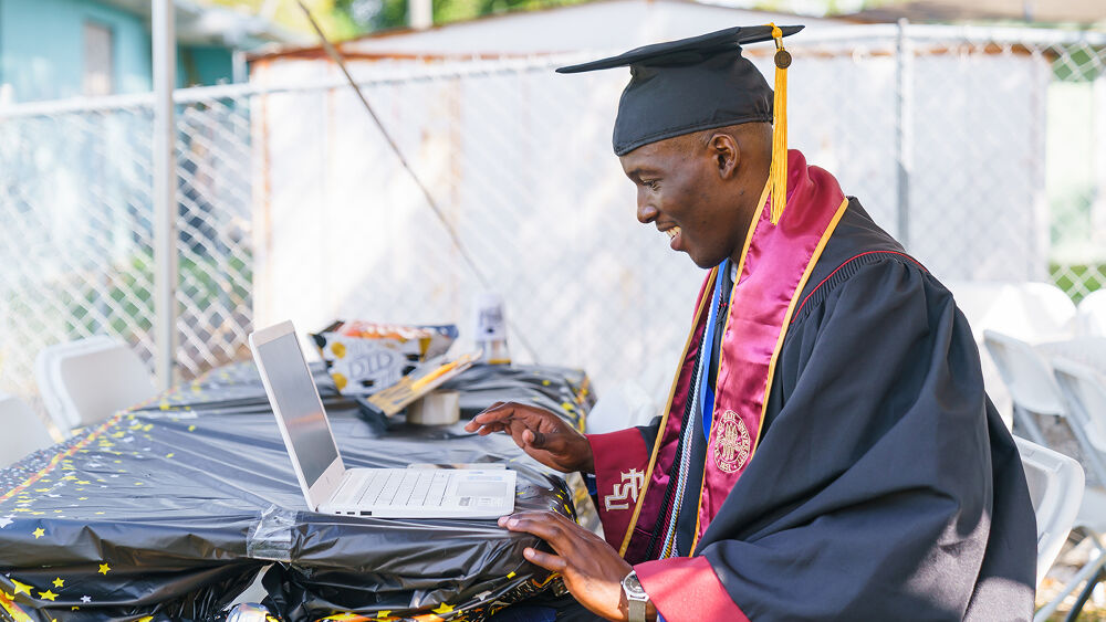 Man working on laptop in cap and gown