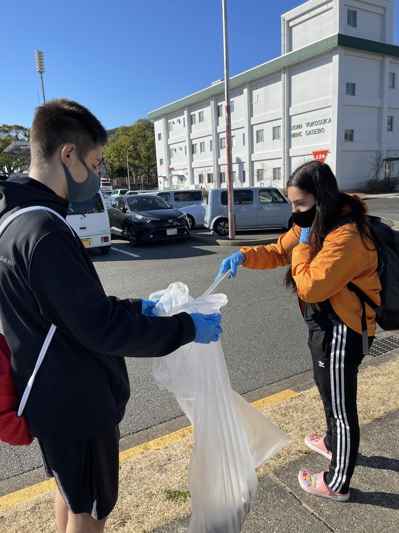 2 teen volunteers picking up trash