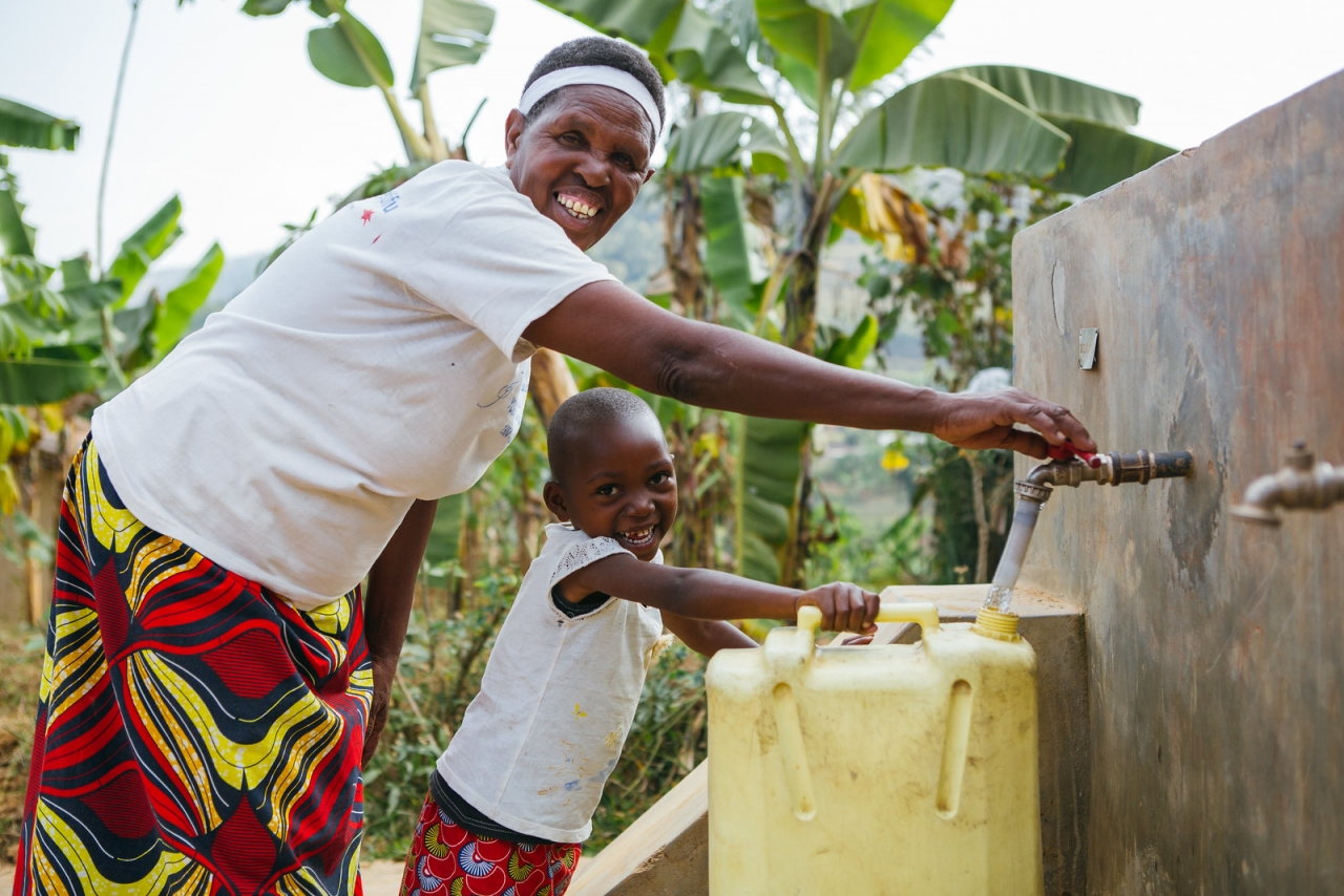 A woman and her granddaughter access safe water in rural Rwanda. Photo credit: Water For People
