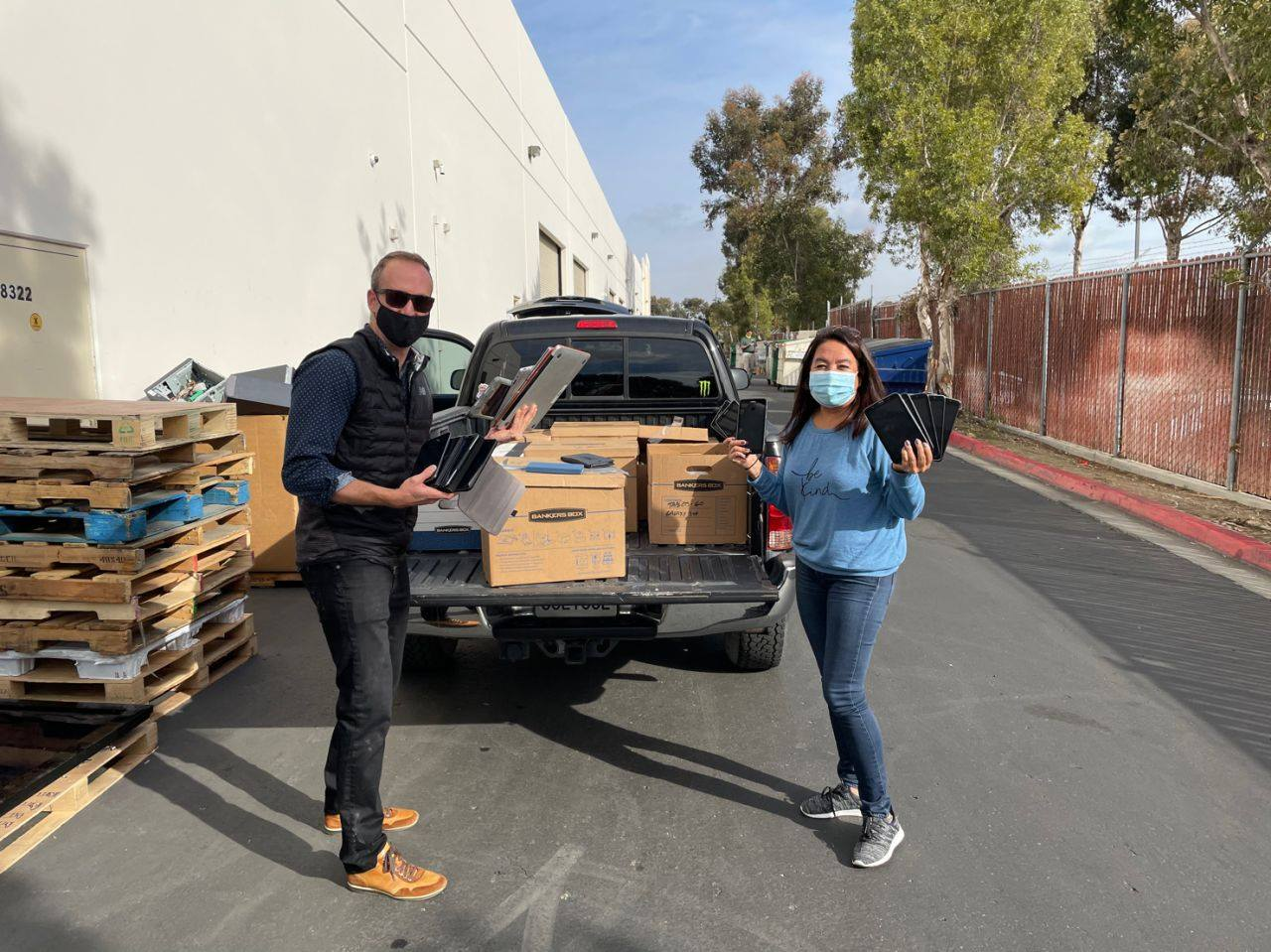 Jeff Monday (L), Qualcomm Vice President of Sales, helps Vida Roozen (R) of Creative Channel Services unload over 300 computers, tablets, headphones, monitors, and printers that Creative Channel Services, graciously donated.